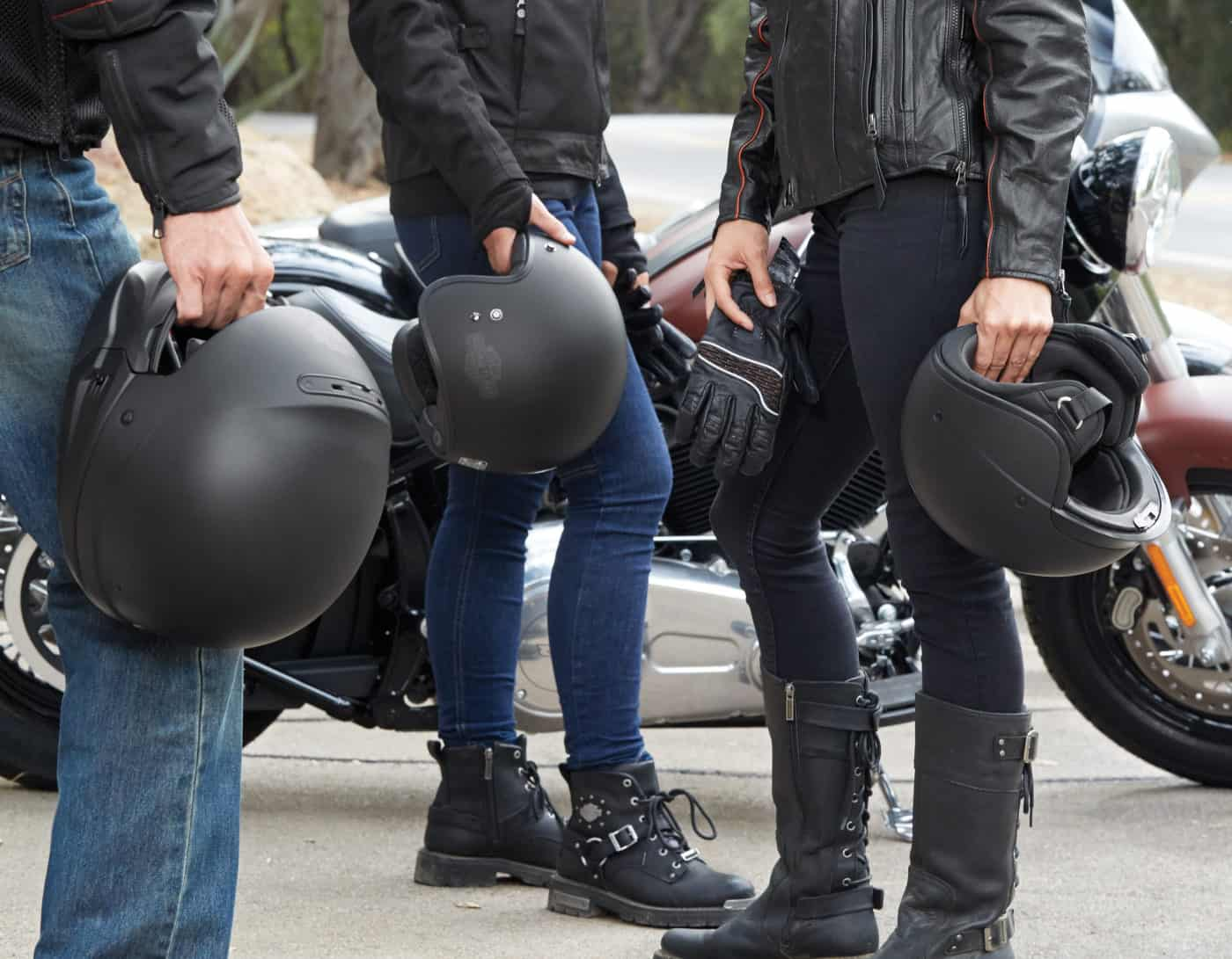Friends with different types of motorcycle helmets in their hands.